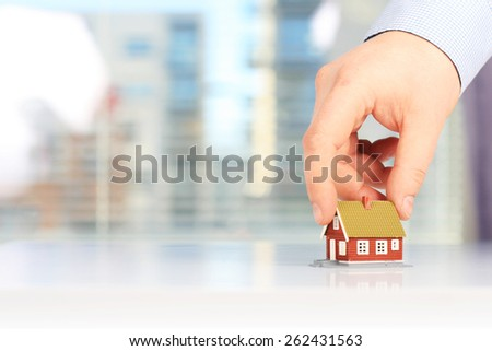 Real estate concept. Hand is giving a house.