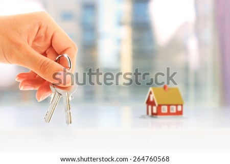 Real estate concept. Hand with key and new house.