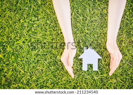 Real estate concept - hands of a young woman surround a white cutout house over green grass, copy space available. - stock photo