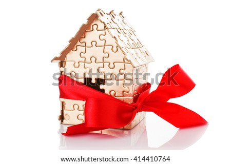 Real estate concept - house of gold color puzzles with red bow - stock photo