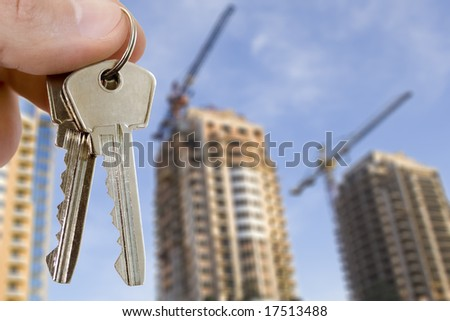 real estate concept. key in fingers with houses - stock photo