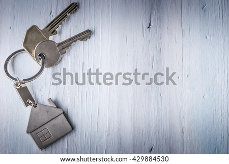 Real estate concept - Key ring and keys on white wooden background - Low key light - stock photo