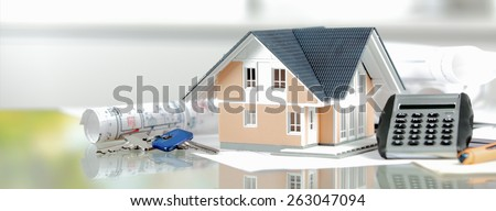 Real Estate Concept - Miniature Model House on Top of a Glass Table with Calculator, Keys and Blueprint. - stock photo