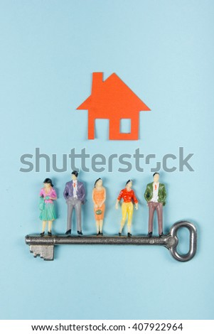 Real Estate concept. Model house, construction, house building. Paper house and people figures with key on blue background. Top view. Copy space for text - stock photo