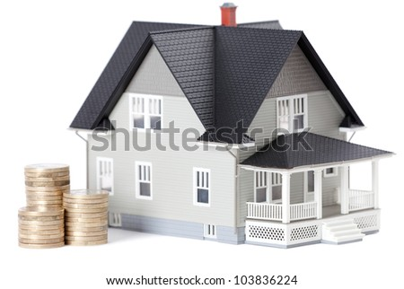 Real estate concept - stacks of coins in front of home architectural model, isolated - stock photo