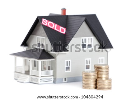 Real estate concept - stacks of coins in front of household architectural model, isolated - stock photo