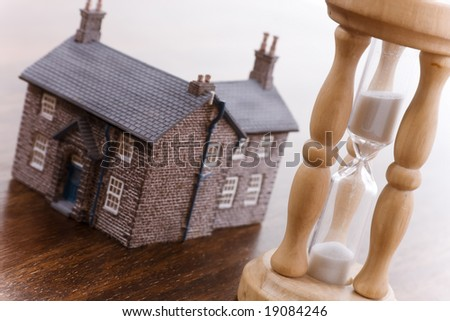 Real estate concept time running out focus on hourglass - stock photo