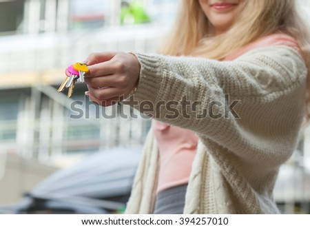 Real estate concept - young woman on front of new big modern house building construction site with keys - stock photo