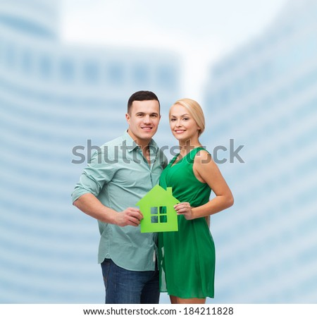real estate, family and couple concept - smiling couple holding green paper house - stock photo