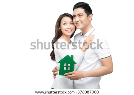 real estate, family and couple concept - smiling couple hugging with symbol house and key daydreaming at home - stock photo