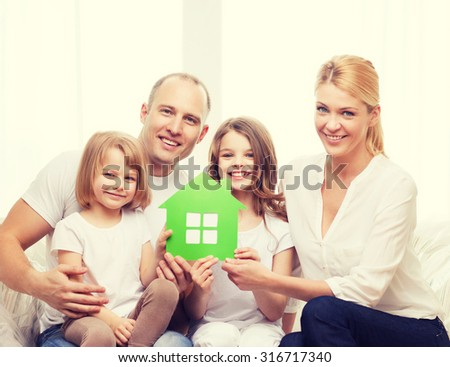 real estate, family, children and home concept - smiling parents and two little girls holding green house - stock photo