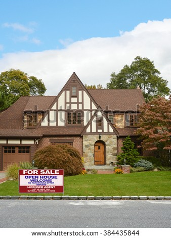 Real estate for sale open house (let us help you buy sell your next home) welcome sign Beautiful Tudor Style Suburban Home Residential Neighborhood Blue Sky Clouds USA - stock photo