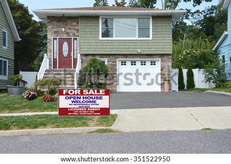 Real estate for sale open house welcome sign Beautiful Brownstone home with flowers blacktop driveway residential neighborhood USA - stock photo