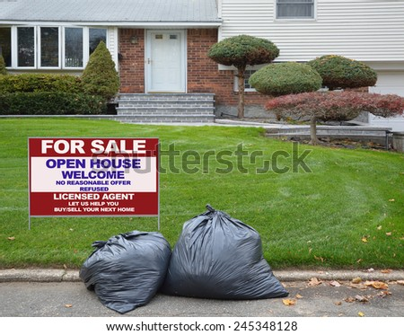Real Estate for sale open house welcome sign behind black plastic Trash bags curbside suburban home residential neighborhood USA