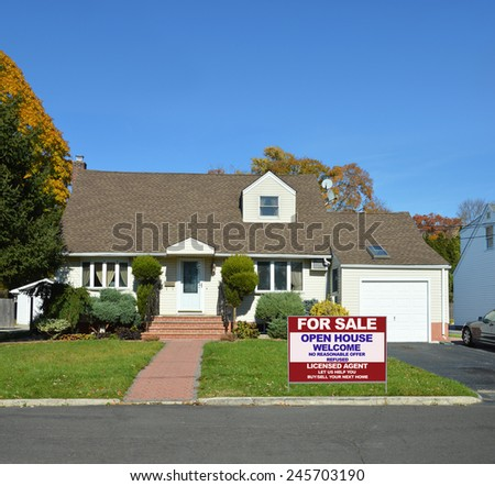 Real estate for sale open house welcome sign on front yard lawn of Suburban cape cod style home sunny clear blue sky autumn day residential neighborhood USA - stock photo