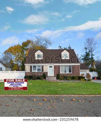 Real Estate for sale  open house welcome sign suburban cape cod style home residential neighborhood autumn day blue sky clouds USA