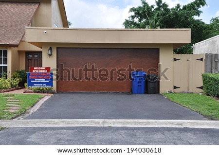 Real Estate For Sale Open House Welcome sign Suburban Home Two Car Garage Recycle Trash Container residential neighborhood USA
