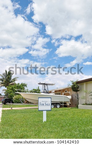 Real Estate For Sale Sign Suburban Home with Boat
