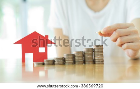 Real estate investment. House and coins on table. - stock photo