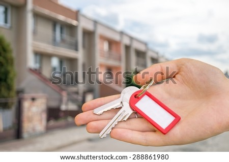 Real estate is selling house and holds keys in hand - stock photo