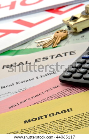 Real estate listing and home seller disclosure broker documents with financial lender mortgage paperwork on busy Realtor desk with keys and sale sign riders in realty agent office