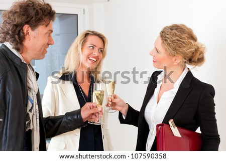 Real estate market - young couple looking for real estate to rent or buy, they celebrate with champagne and clinking glasses - stock photo
