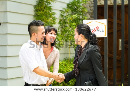 Real estate market - young Indonesian couple looking for real estate apartment or house to rent or buy, the realtor and the client shaking hands