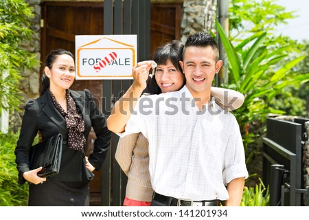 Real estate market - young Indonesian couple looking for real estate apartment or house to rent or buy, the woman holding the keys - stock photo
