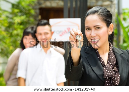 Real estate market - young Indonesian couple looking for real estate apartment or house to rent or buy, the realtor holding the keys - stock photo
