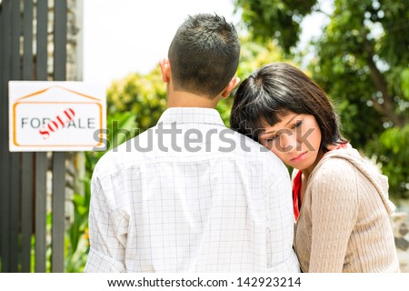 Real estate market - young Indonesian couple looking for real estate apartment or house to rent or buy, they came too late, it is sold or leased - stock photo