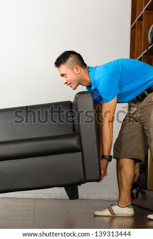 Real estate market - Young Indonesian man lifting a sofa put it away