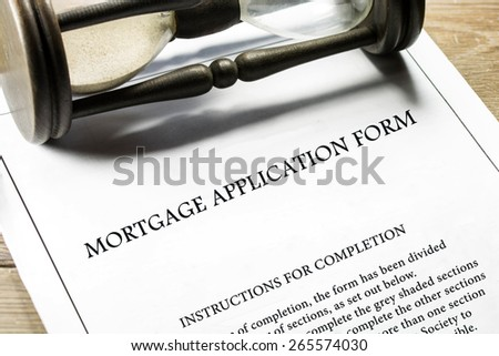 Real estate mortgage application form, instructions for completion and hourglass in the background. - stock photo