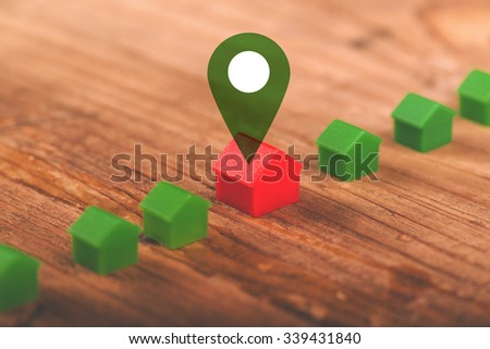 Real estate mortgage concept with small plastic house models on wooden desk - stock photo