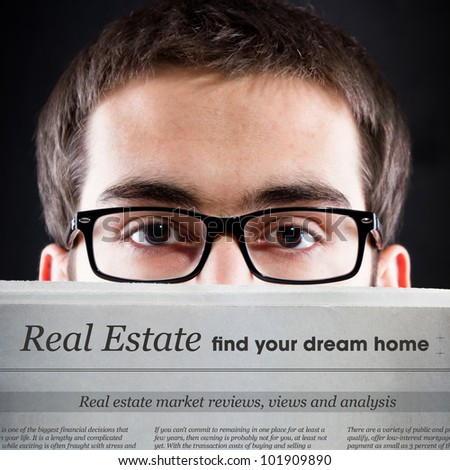 Real Estate News. Young adult looking for real estate news. - stock photo