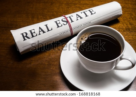 real estate newspaper, cup of coffee on desk - stock photo