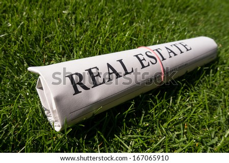 real estate newspaper on green meadow - stock photo