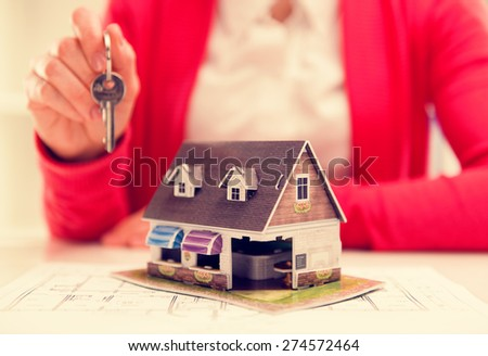 Real estate seller with house model and key. Rent, sale and insurance concept. Shallow depth of field. - stock photo