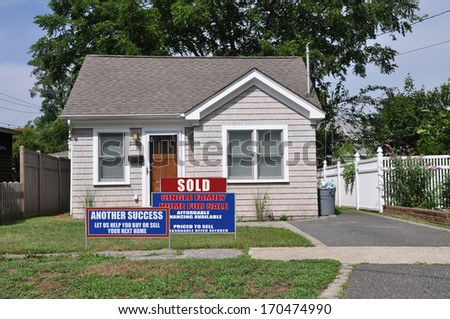Real Estate Sign Sold (Another Success Let Us Help You Buy Sell your next home) Suburban Bungalow home residential neighborhood USA - stock photo
