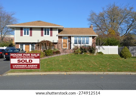 Real estate sold (another success let us help you buy sell your next home) sign Beautiful High Ranch Home Sunny Clear Blue Sky residential neighborhood USA - stock photo