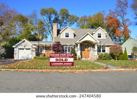 Real estate sold (another success let us help you buy sell your next home) sign beautiful suburban cape cod style home autumn clear blue sky day residential neighborhood USA - stock photo