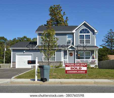 Real estate sold (another success let us help you buy sell your next home) sign Beautiful Suburban Home Clear Blue Sky Day Sunny Residential Neighborhood USA - stock photo