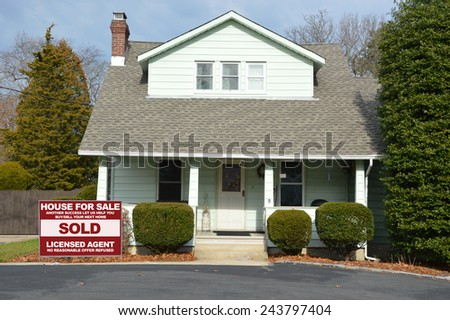 Real estate sold (another success let us help you buy sell your next home) sign Suburban Bungalow style home with blacktop driveway residential neighborhood USA - stock photo