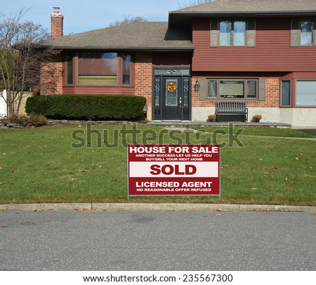 Real estate sold (another success let us help you buy sell your next home) sign Suburban high ranch house residential neighborhood USA - stock photo