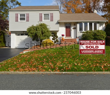 Real Estate sold (another success let us help you buy sell your next home) sign Suburban high ranch house autumn day residential neighborhood USA