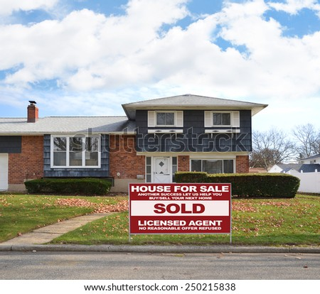 Real estate sold (another success let us help you buy sell your next home) sign Suburban high ranch brick home autumn blue sky clouds day residential neighborhood USA - stock photo
