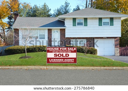 Real estate sold (another success let us help you buy sell your next home) sign Suburban High Ranch Home Twilight Autumn Day Residential Neighborhood USA - stock photo
