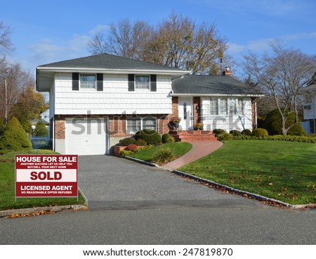 Real estate sold (another success let us help you buy sell your next home) sign Suburban home autumn day residential neighborhood USA - stock photo