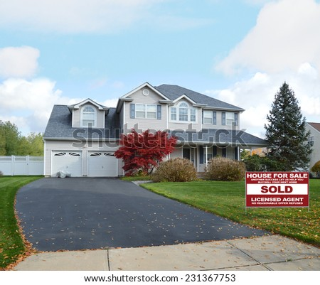 Real Estate Sold (another success let us help you buy sell your next home) sign suburban mcmansion style home autumn day residential neighborhood blue sky clouds USA