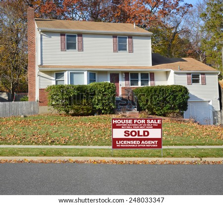 Real estate sold (another success let us help you buy sell your next home) sign Suburban Tan High Ranch home with leaves on front lawn autumn day residential neighborhood Sunny blue sky