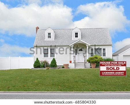 Real Estate sold sign White Suburban bungalow home blue sky clouds USA